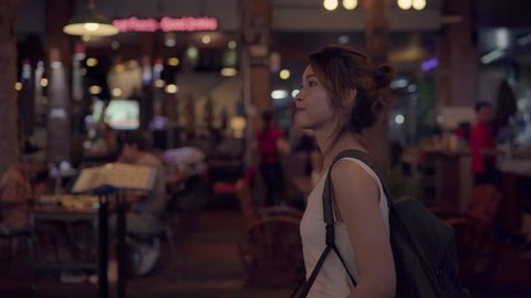 Traveler backpacker asian woman travel in Khao San road at Bangkok, Thailand. Happy young female spending holiday trip at amazing landmark and enjoy her journey traditional city in the night.