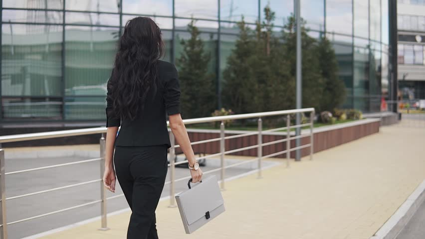 Portrait of young confident business woman in suit with folder for papers in hands. a girl in a trouser suit walks down the street. back view | Shutterstock HD Video #1015008370