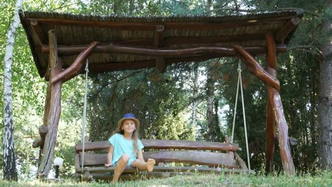 Portrait of happy young girl swinging on sunny day in park.