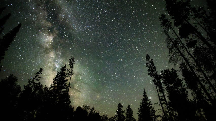 Time lapse of the Milky Way moving through the sky viewing airglow moving over the galaxy from within a forest.