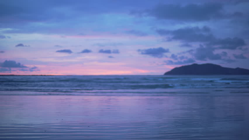 Out of focus background plate of pretty purple and blue sunset on the beach in Costa Rica for compositing or keying. Blurred or defocused shot of ocean sun set for green screen composite. 4k