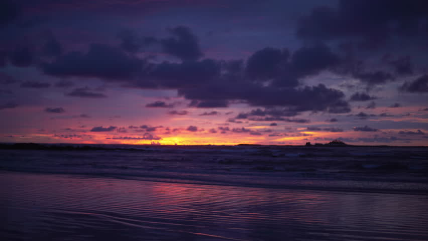Out of focus background plate of dark purple and orange sunset on the beach in Costa Rica for compositing or keying. Blurred or defocused shot of ocean sun set for green screen composite. 4k