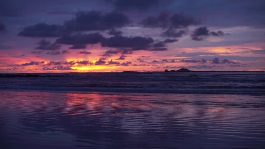 Out of focus background plate of gorgeous orange, purple and blue sunset on the beach in Costa Rica for compositing or keying. Blurred or defocused shot of ocean sun set for green screen composite. 4k