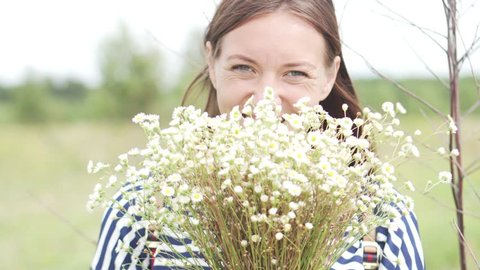 A woman is standing in a field with a bouquet of field chamomiles. Close-up. She has a big bouquet in her chickens. A woman is smiling and playful hiding a smile behind a bouquet. No makeup, no hair.