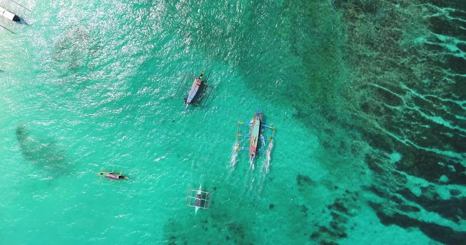 Aerial bird's eye view over boats sailing off the coast of Boracay in the Philippines