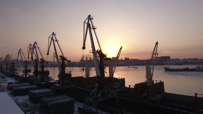 Aerial Approach Cranes commercial port steel Sunset orange Golden horn Bay Industrial business quiet scenic waterfront. Urban landscape. Vladivostok Russia. Tourism landmark. Winter snow frozen. Drone