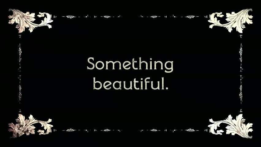 A re-created film frame from the silent movies era, showing an intertitle text: Something Beautiful.