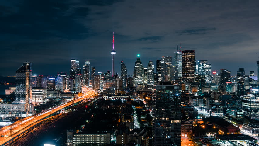 Huge epic wide city skyline views at night of the Toronto Canada downtown core. Office buildings, condominiums and urban modern architecture layer the skyline. Gardiner Expressway car traffic. | Shutterstock HD Video #1015058800