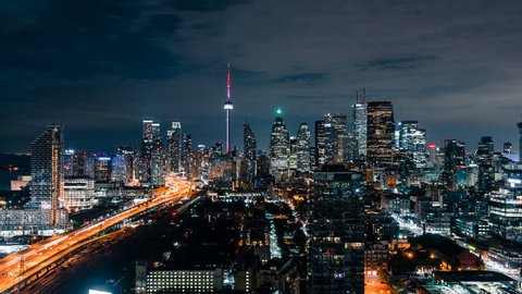 Huge epic wide city skyline views at night of the Toronto Canada downtown core. Office buildings, condominiums and urban modern architecture layer the skyline. Gardiner Expressway car traffic.