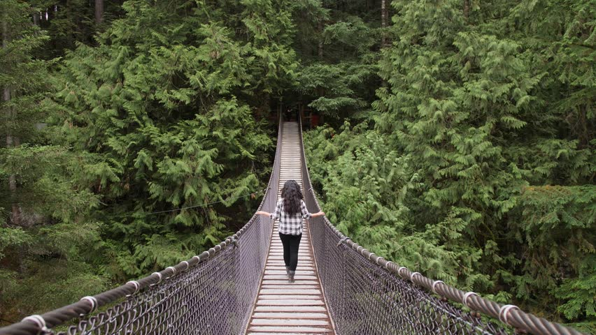 Woman Walking Along Suspension Bridge Alone in Picturesque Green Forest Setting. Lynn Canyon Vancouver, British Columbia, Canada. Surround by Rich Green Trees. | Shutterstock HD Video #1015059490