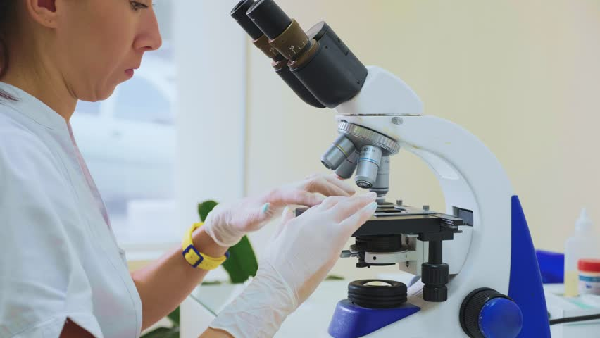 Young attractive veterinary worker in gloves using microscope for testing blood samples of animals. Vet doctor looking into microscope, close-up. #1015093540