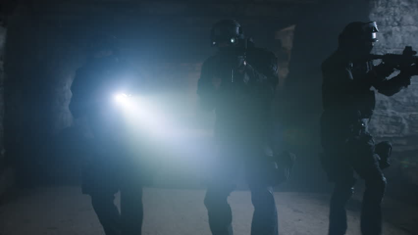 Members of a SWAT police team investigating a dark warehouse with flashlights and guns and finds a member tied to a chair. Shot with a RED camera. 4k footage.