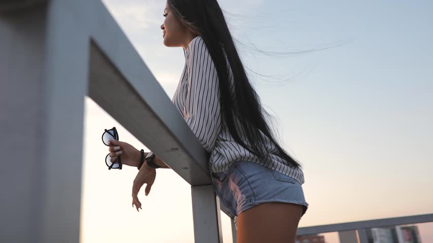 Woman relaxes looking to cityscape from rooftop in sunset time