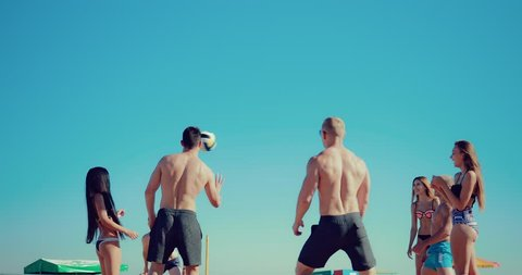 Group of young girls and guys playing beach volleyball. Slow motion