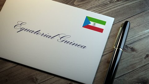 Country name written on a card or envelope in cursive font with a sleek pen on a wooden table surface under beautiful classy light. Stamp in the corner shows the flag of Equatorial Guinea