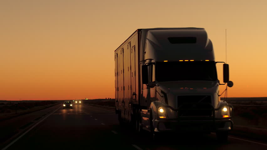 CLOSE UP: Freight container semi trailer truck transporting goods. Cars on road trip driving along the beautiful country highway after the sunset. Lorry shipping cargo, people traveling by night
