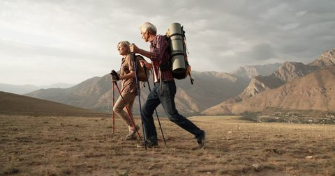 Old caucasian couple hiking, trekking in mountains with backpacks, enjoying their adventure - tourism concept 4k