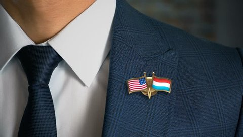 Businessman Walking Towards Camera With Friend Country Flags Pin United States of America - Luxembourg