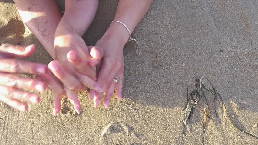 hands touching each other on the sand at the beach #1015192030