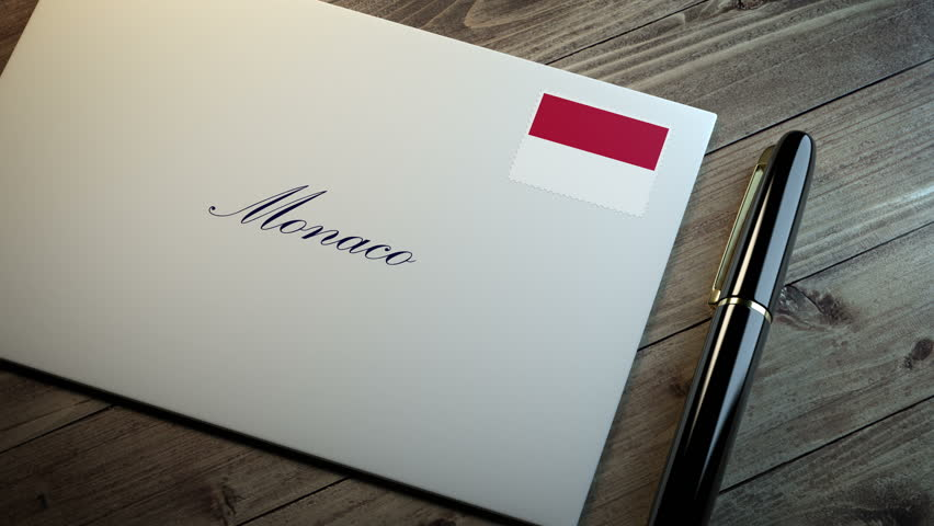 Country name written on a card or envelope in cursive font with a sleek pen on a wooden table surface under beautiful classy light. Stamp in the corner shows the flag of Monaco