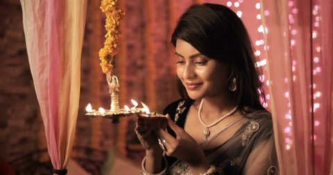 A beautiful and traditional woman lighting a lamp (Diya) during Diwali festival. A nice looking female in a sari lights the hanging oil lamp and smiles in a house decorated with lights and flowers