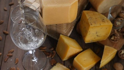 Cheese and wine. Variety of cheese placed on wooden background. wine is being poured into wine glass in slow motion