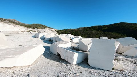 Walk POV at industrial marble quarry site with huge marble blocks