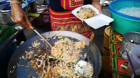 Stir fry cooking and then serving the famous Thai meal called  'Pad Thai noodles' in a large wok, cooked then scooped on to a polystyrene dish at a typical street food market in Thailand.