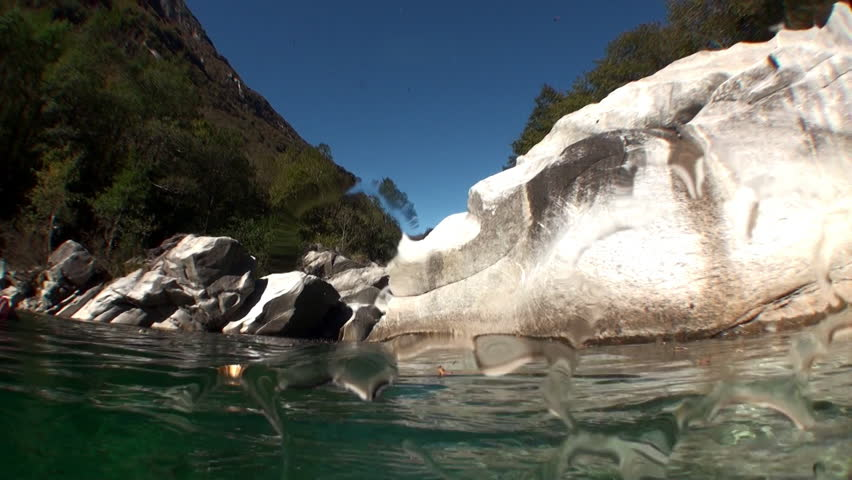 Transparent water of river Verzasca on background of huge smooth stones Picturesque nature and beautiful landscape in canton of Ticino are favorite place for underwater photographers. | Shutterstock HD Video #1015244080
