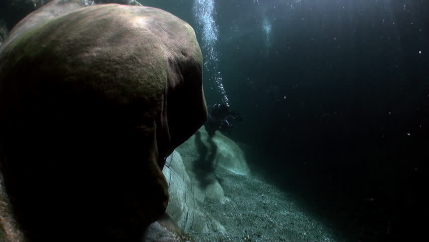 Camera operator in refraction of sunlight underwater in transparent river. Shooting a frame of picturesque nature on background of huge smooth stones in Verzasca. | Shutterstock HD Video #1015244230