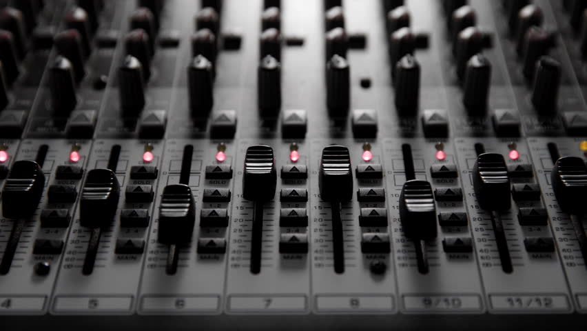 Audio mixer; hand fading down level of two channel simultaneously. #1015293070