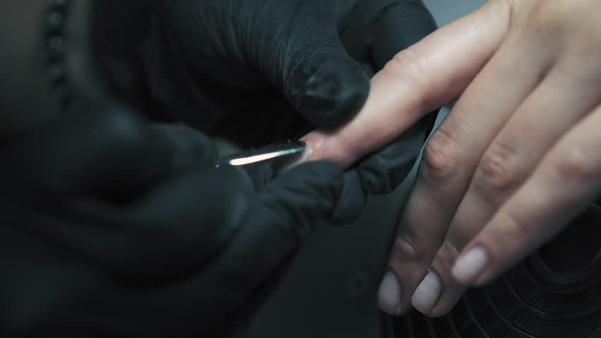 Professional nail care in beauty salon. Beautician in black gloves is using cuticle pusher for pushing cuticles on client finger. Nail service.