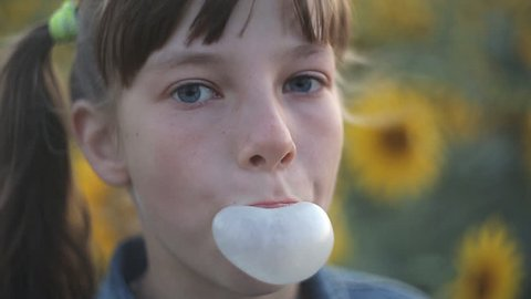 Beautiful teen girl inflating bubble of chewing gum. Moderm fashion girl.
