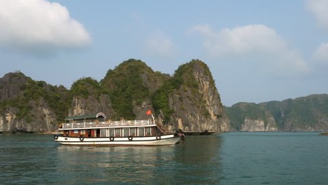 TOURISTS AND CRUISE BOAT IN HA LONG BAY, CAT BA NATIONAL PARK, NORTH EAST VIETNAM – 4 APRIL 2018 The limestone islands in UNESCO World  Heritage site, Ha Long Bay, Cat Ba National Park, Vietnam