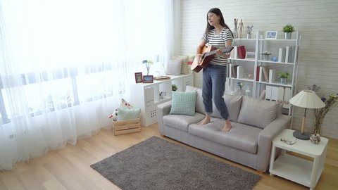 c53493b12d Asian woman holding her wooden guitar and jumped down from the sofa in the  living room