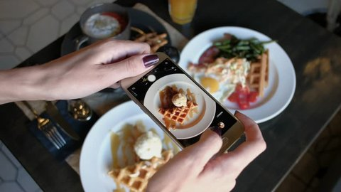 Female hands photographing appetizing food by smartphone in the restaurant.