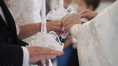 Priest praying in church at wedding ceremony and put on rings for newlyweds bride and groom