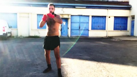 Boxer training in Slow Motion  - Urban fighter in Shadow boxing - Sequence fixed, slow motion, full face - training of a boxer on the street before a fight