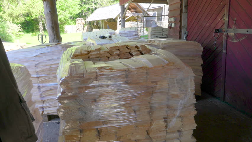 Hundreds of wooden shingles piled up on the ground with the roll pf plastic wrap on the top