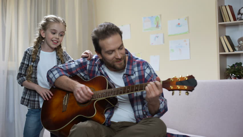 Talented girl singing while father playing guitar, home concert, musical hobby #1015344040