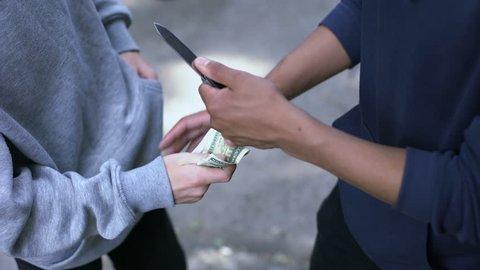 Teenager threatening boy with knife, extorting money, street robbery, closeup