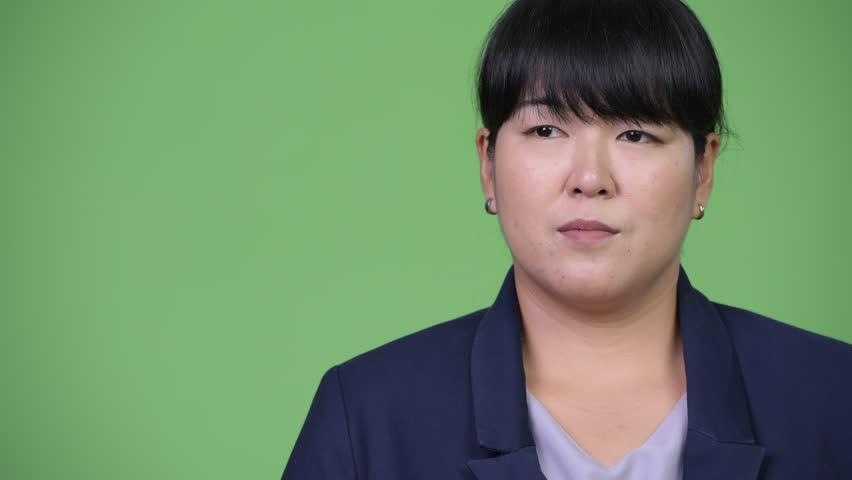 Head shot of beautiful overweight Asian businesswoman thinking | Shutterstock HD Video #1015376050