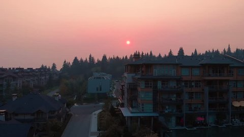 Aerial shot over apartment complex over a smoke obscured view of Vancouver during the 2018 wildfire season.