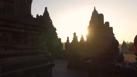 Forward dolly cinematic shot of Prambanan Temple in the morning with sun rising behing the temple and stupa