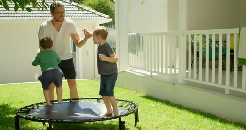 Father playing with kids on trampoline in home yard 4k