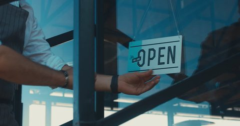 Caucasian male turning sign from closed to open on the entrance door of his small cafe. Small business concept. 4K UHD 60 FPS SLOW MOTION