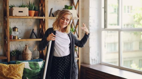 Attractive young lady is having fun during clean-up, she is singing and dancing with mop enjoying music in headphones. People, interiors and joy concept.