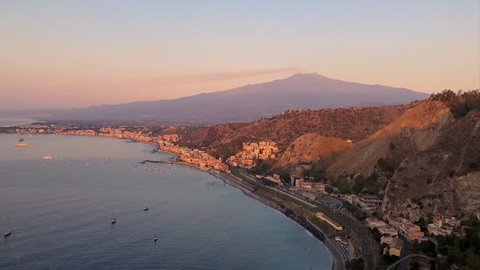 View of the city of Taormina and active volcano Etna at sunrise. Delightful morning scenery on the town of Taormina and the volcano Etna. Sicily, Italy