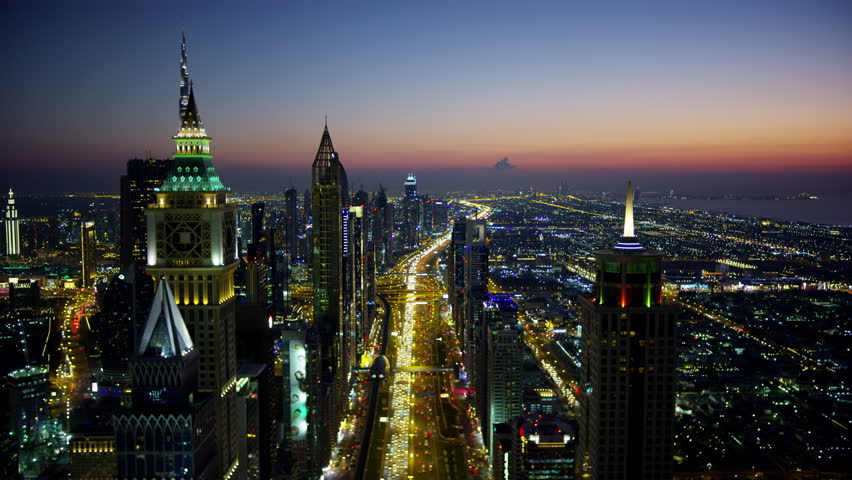 Aerial night illuminated city view Sheikh Zayed road commercial condominium district vehicle transport highway metro rail UAE Middle East Dubai RED WEAPON