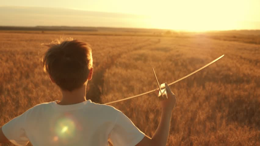Happy child runs with a toy airplane on a sunset background over a field. The concept of a happy family. Childhood dreams
